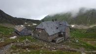 Podragu-Hütte. Rechts davon einer der Streich-Helferlinge im weißen Ganzkörperanzug
